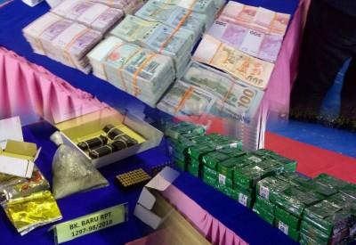 警方周六在记者会出示在行动中搜到的冰毒、炼毒工具、一把半自动手枪、子弹、金饰和多国纸钞。