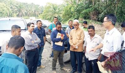 李凯伦(右)、瓜拉打昔村长扎沙曼(右3)、官员们以及社委会正在讨论润绒河的河堤崩塌问题。
