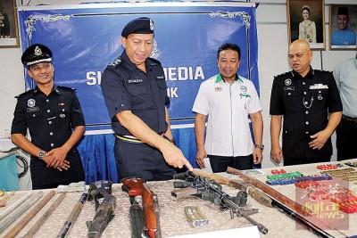 祖基菲(左2)展示嫌犯所使用自制及改裝猎枪进行猎杀野生动物活动,并指着其中一把疑是M16來福枪。左3是阿都卡迪。