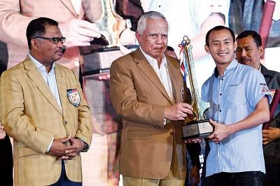 胡满化(右)从甲州首长敦卡里尔雅谷(中)手中接过奖杯。