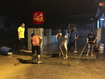 居民在水势退后漏夜清理屋子。