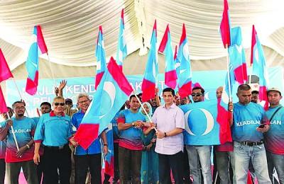 阿兹敏将旗帜移交予槟榔东海州议席竞选主席慕哈斯迪及团队,曼梳(前左2起)和查基等陪同。