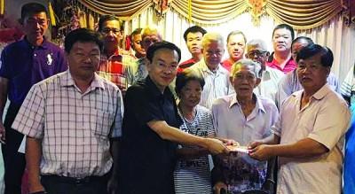 陈栋良(左2)在理事会成员联合见证下,移交1000令吉捐款予曾庆健。