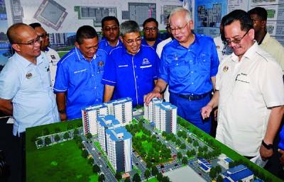 纳吉以吉大臣阿末峇沙的伴随下参观峇卡峇打人民房屋计划模型。