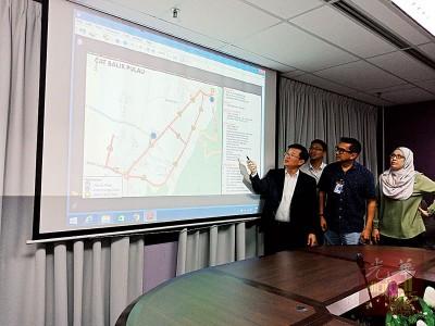 曹观友(左)向媒体讲解浮罗山背免费巴士接驳服务的路线。