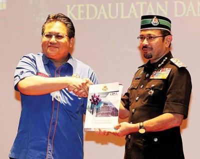 承诺查兹兰(左)也移民局的马来西亚签证指南主持推介仪式后,得到慕斯达法阿里赠送该本指南。