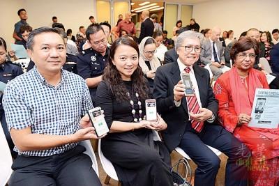 黄思汉(左起)、杨巧双、彭江生与艾吉尔鼓励民众下载「成为我的保护者」手机应用程式,一齐打击人口贩卖案。