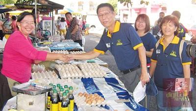 许汉宏(右3)与巴刹小贩握手交流。