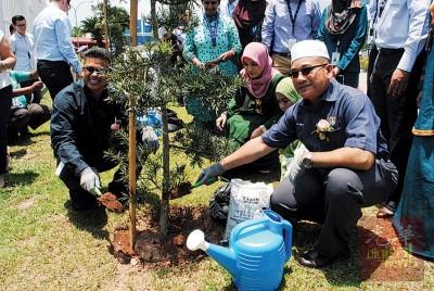 罗查里(右)及威斯哇那仁参与植树计划,为2018地球日挑战活动写下页章。