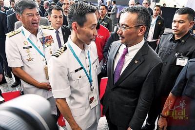 """希山慕丁(右起)在第16届亚洲防务展上,与也是马来西亚海军志愿后备军名誉少校的我国羽毛球""""一哥""""拿督李宗伟寒暄。左为海军司令丹斯里阿末卡玛鲁再曼。"""