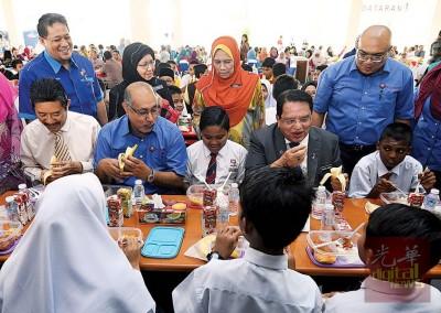 东姑安南(坐者右2)食物援助推介礼后,与学生们进餐。左起是阿南末依斯汉及赛阿里。