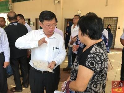 曹观友(左)耐心向不了解免费接驳巴士服务路线图的民众讲解。