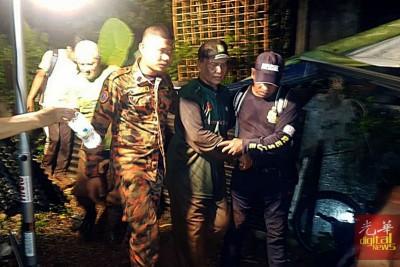 搜救人员合力扶一名登山客离开山林。(照片取自消拯局脸书)