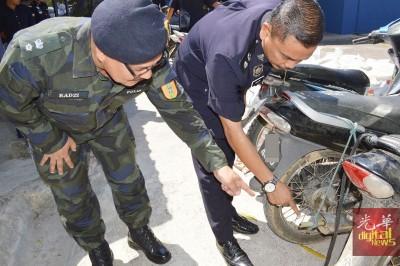 莫哈末哈林警监(右)展示走私者将竹支插入摩托车排气管内。
