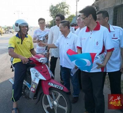 郑成泉一行人持着公正党的党旗,到巴东勿刹街上访问选民。