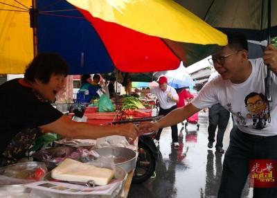 大雨不阻扰!郑来兴及曹观友手持雨伞继续拜票。
