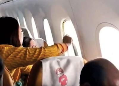空姐把窗装回原位。