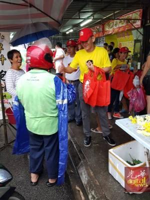 王耶宗冒着雨到大路后巴刹走访拜票,并分派环保袋给民众。