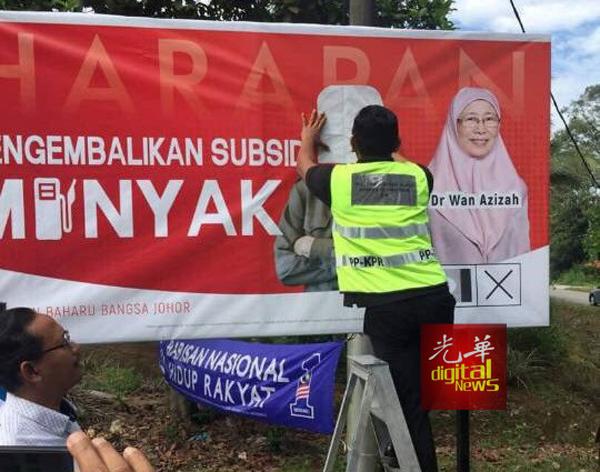 选委会职员在雪州班丹的竞选看板上,以贴纸遮住敦马肖像头部及名字字眼。