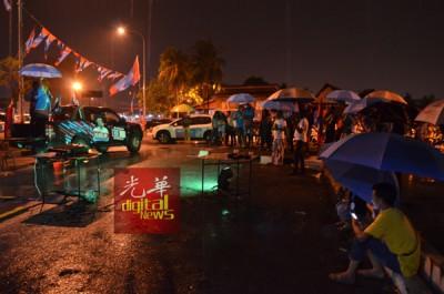 支持者在风雨中仍不离不弃,驻足聆听希望联盟讲座。