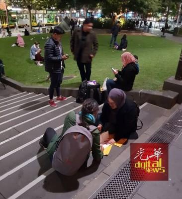 身在澳洲的海外选民席地而坐填写邮寄选票,准备托回国的大马人送到选举官手上,履行身为大马公民的义务。(图取自Joshua Ong家和脸书)