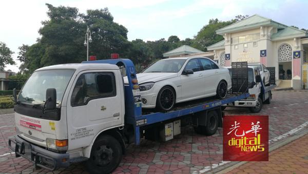 两辆拖车载走白色的马赛地轿车。