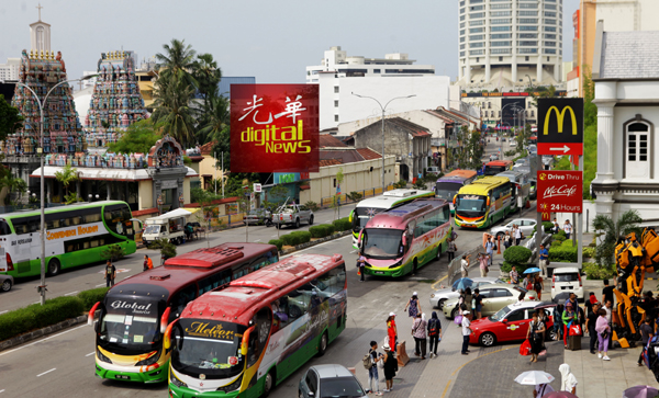 路边停满巴士,一些旅巴在路中间让旅客上下巴士。