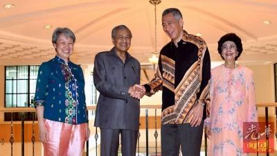 马哈迪(左2起)接待与李显龙,握手示好。左起是何晶及西蒂哈斯玛。