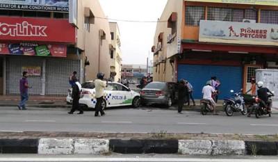 警车与匪车相撞,公众案发后在现场驻守围观。