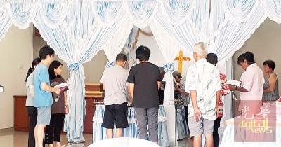 死者家人诵圣经。