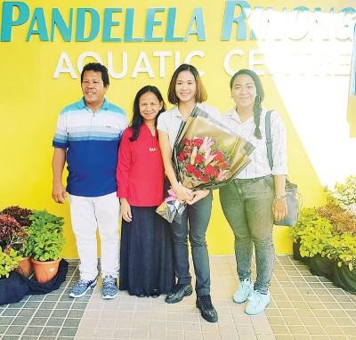 潘德蕾拉喜捧花束,与家人在以她名字冠名的砂拉越水上中心合影留念。