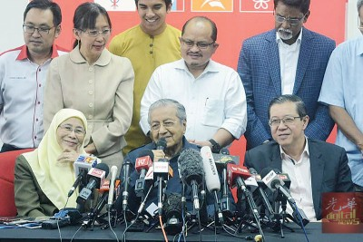 马哈迪(中)宣布兼任教长,旺阿兹莎(左)则兼任妇女及福利部长。右为候任财长林冠英。