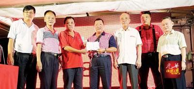 《光华日报》代表(左3)将筹获的190令吉义款移交予郭明福(左4),由杨建发(左起)、邱继溢、陈来福、许友帼及戴良成见证。