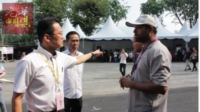 杨顺兴(左)位于垄尾日月城夜市空地投票中心站时,因多项问题与选举官员起争执。