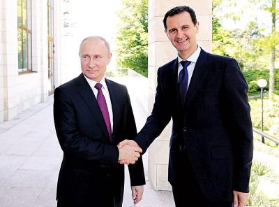 普京(左)和阿萨德握手。(法新社照片)