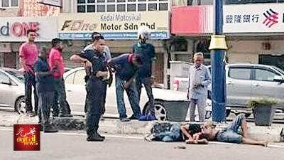 两名匪徒卧躺在地,警员在场驻守防止他们逃走。