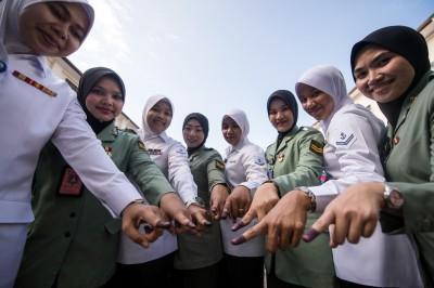 军警周六上午8时开始提前投票,图为隆市峇当登巴路的柯孟达军营(Kem Kementah)军人在投票后展示已点墨的指头。