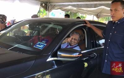 乘坐在驾车上的敦马哈迪示出染墨的手指。
