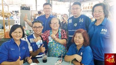 殊不知象过河流来到槟岛,吴秀丽(左)看时也不忘分派名片给选民。