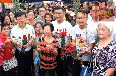曹观友(左2)、郑来兴(右3)及魏子森(右2)送花予妇女们。