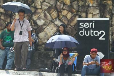 烈阳高空,媒体撑着雨伞遮阳,席地而坐。