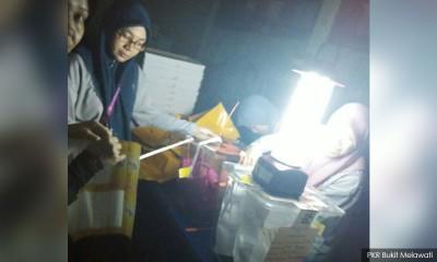 祖微丽亚的监票员提供照片显示,选委会官员在 黑暗中,透过手电筒灯光计票。