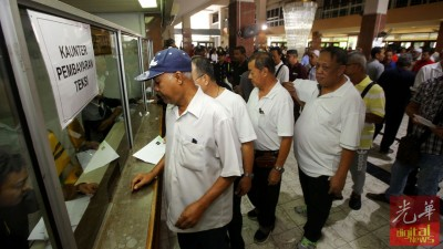的士司机在槟州大会堂柜台处排队领取奖励金。