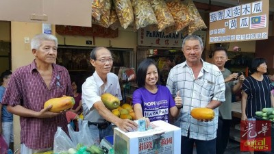 """(右2从)上丽丽、罗盛泉应义卖,捐款""""救国""""。左为洪顺进,右为甘榜峇汝社委会主席陈汉荣。"""