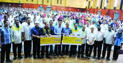 扎基尤丁(右7)代表槟州政府移交模拟支票予阿都马烈达鲁期(右5)以及刘廷深(左5),众行政议员、候任州议员及政府官员等陪同。