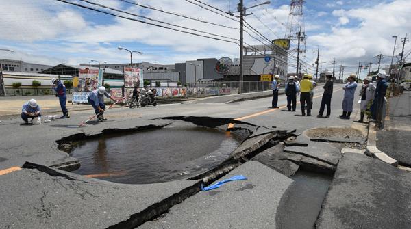 高槻市水管破裂,射出数米高的水柱并造成路面塌陷。(法新社照片)