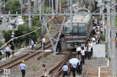 列车停驶后,上班族徒步走回车站。(法新社照片)