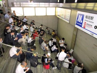 由于列车服务暂停,民众在梅田站外等候。(法新社照片)