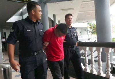 被告在推事做出裁决后被带离法庭,低头避开镜头。