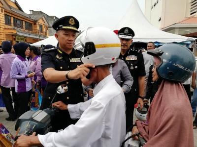 吉州陆路交通局主任苏海米为一名摩托车骑士戴上新头盔。
